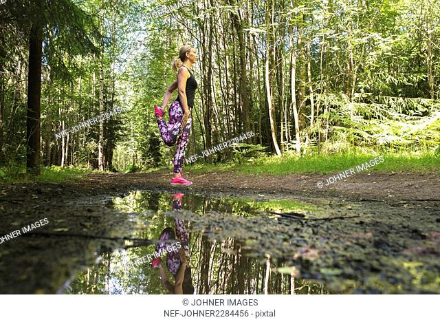 Young woman practicing yoga in forest