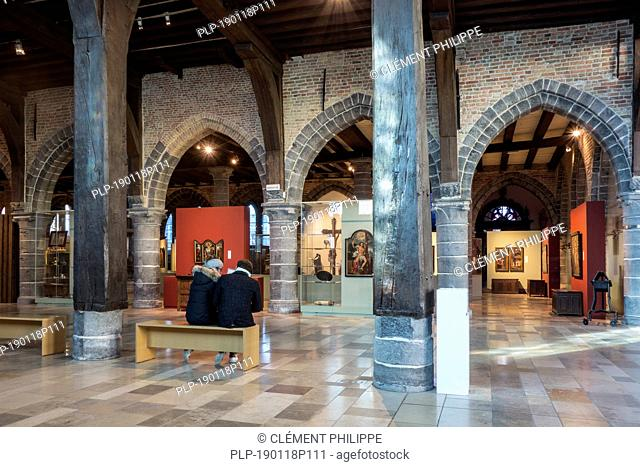 Tourists visiting museum in the old sick-bay at the medieval Sint-Janshospitaal / St John's Hospital in the city Bruges, West Flanders, Belgium
