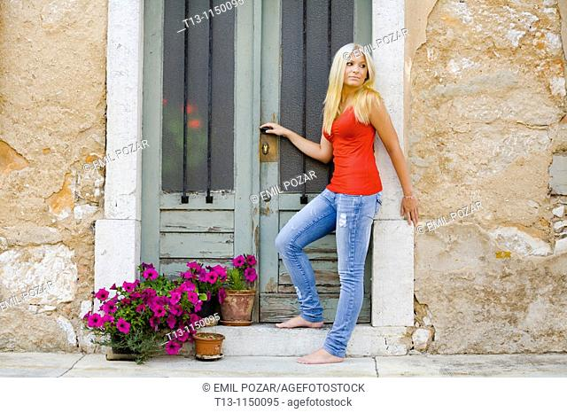 Entering Mediterranean style traditional house young woman