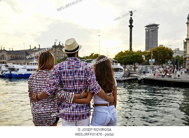 Spain, Barcelona, three tourists embracing at the waterfront in the city