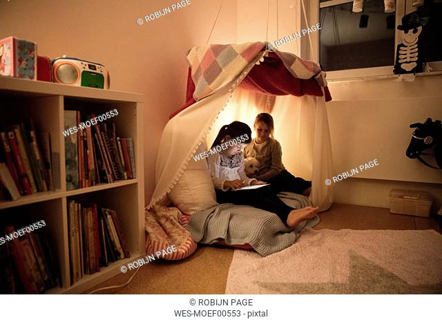 Two girls with dog and tablet in children's room