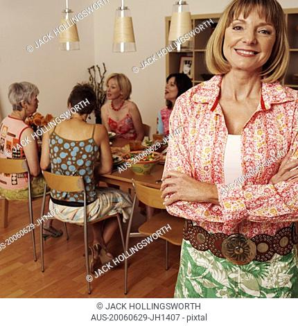 Portrait of a mature woman smiling and her friends sitting at the dining table in the background