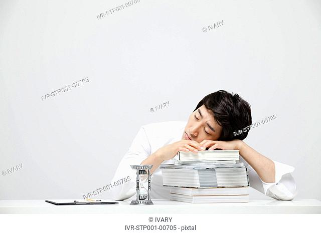 Asian Businessman Leaning Head On Books At Work