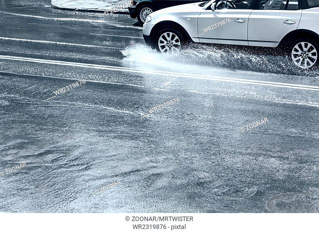 car rides on water in rainy street
