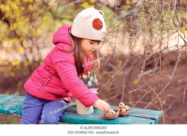 in the park little cute girl wearing hat resting on a wooden bench