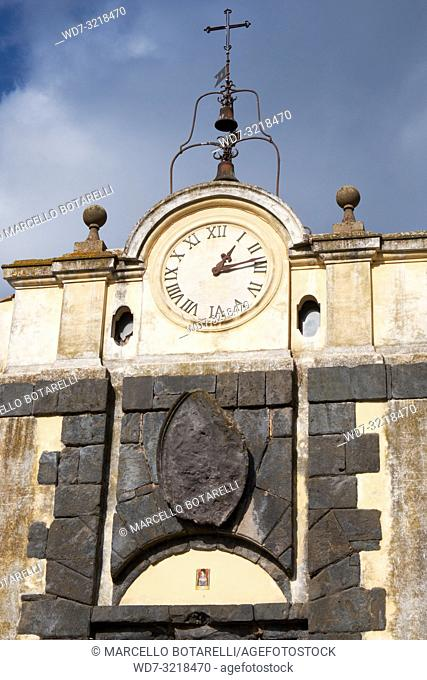 antique clock with bells above the entrance door of the city, anguillara sabazia, lazio, italy
