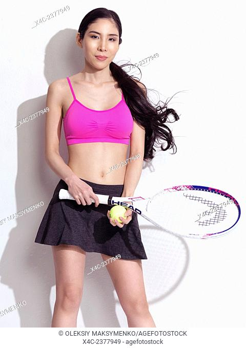 Portrait of a young Japanese woman with a tennis racket wearing a sporty outfit on white background