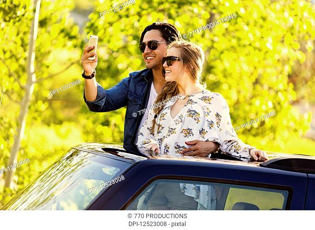 A young couple stand up through the sunroof of their vehicle and take a self-portrait with their cell phone; Edmonton, Alberta, Canada