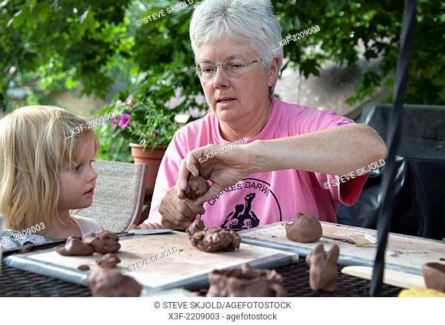 Teacher demonstrating the art of modeling ceramic clay to student age 3 in outdoor backyard class. St Paul Minnesota MN USA