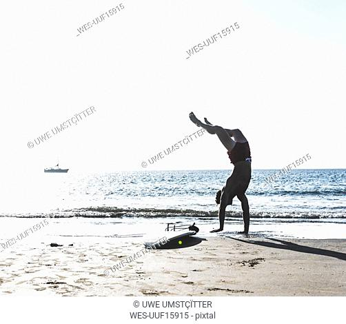 France, Brittany, young man doing a handstand on the beach next to surfboard