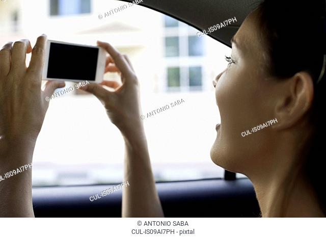 Close up of young woman photographing from taxi window