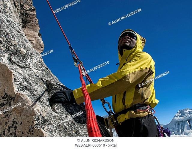 Nepal, Himalaya, Solo Khumbu, Everest region Ama Dablam, mountaineer with rope at rock face looking up