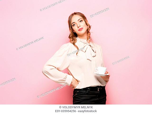 The serious frustrated young beautiful business woman with empty cup on pink studio background