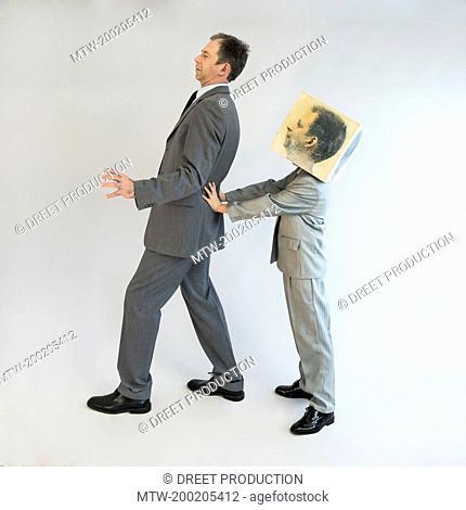 Boy wearing mask pushing businessman