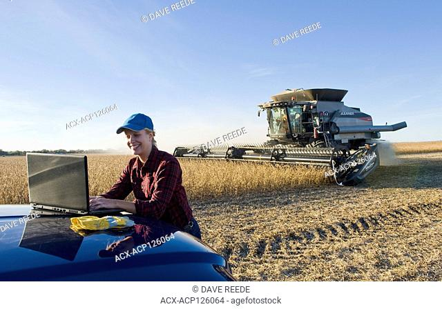 a farm girl uses a laptop computer as a combine harvester work a field during the soybean harvest, near Lorette, Manitoba