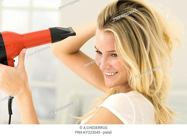 Woman drying her hair with a hair dryer