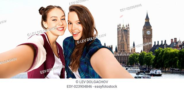 people, travel, tourism and friendship concept - happy smiling pretty teenage girls taking selfie over london background