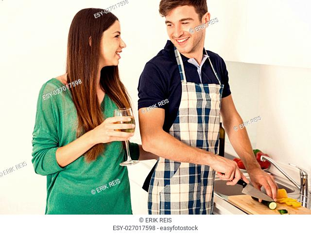 Young couple on the kitchen follow a recipe by tablet and cooking