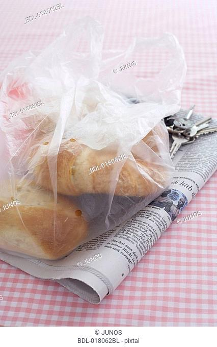 still life of plastic bag with pastries newspaper and keys