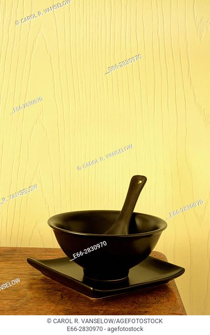 Dark bowl, plate and spoon sitting on corner of wooden table