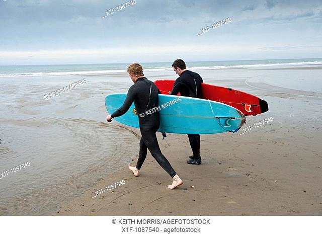 Two men carrying their surfoards, Borth , Ceredigion, West Wales UK