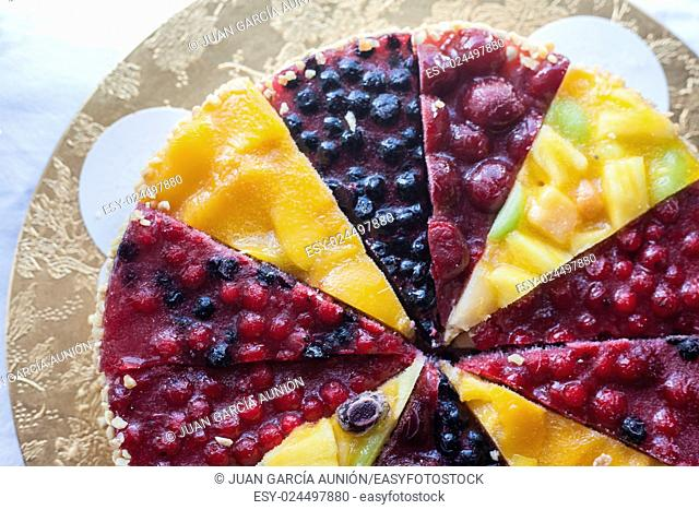 Refreshing tart with frozen berries and fruits over cotton tablecloth. Top view