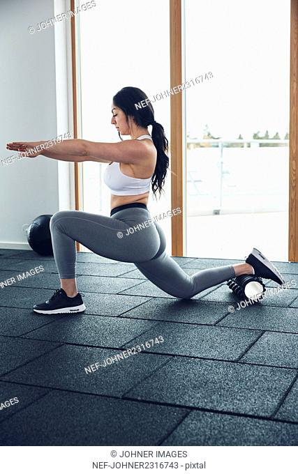 Woman exercising with foam roller