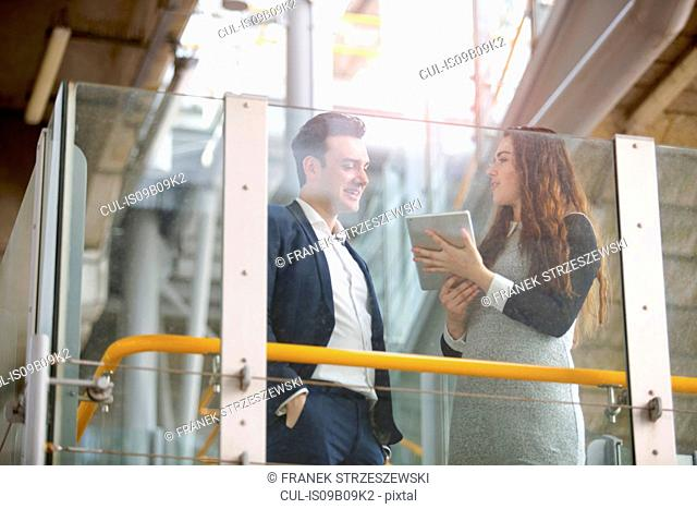 Businessman and woman discussing digital tablet on city stairway, London, UK