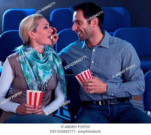 Loving couple sharing their popcorn