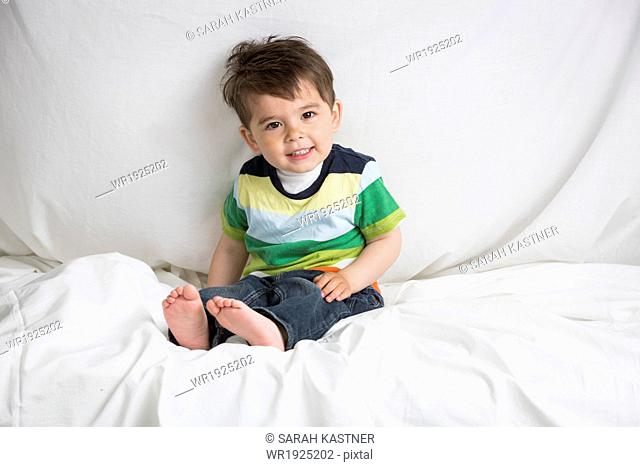 Little boy sitting on a bed