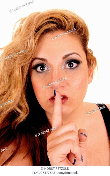 A blond pretty woman with big eye's holding her finger over her mouth.be quiet, isolated for white background.
