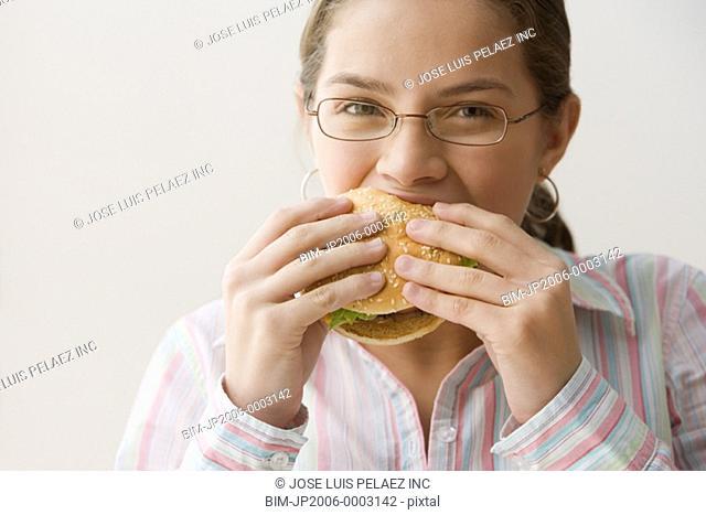 Hispanic girl eating cheeseburger