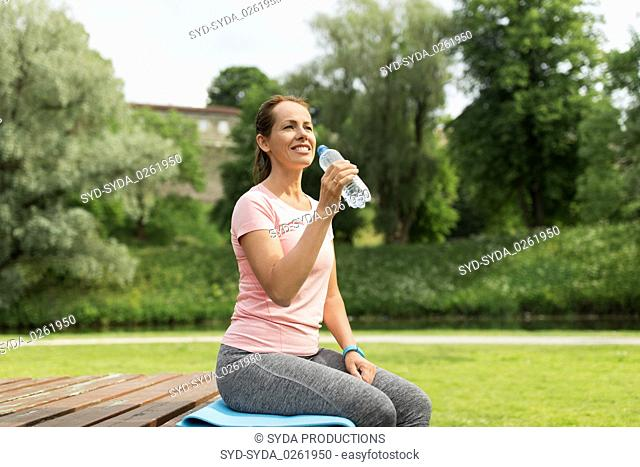 woman drinking water after exercising in park