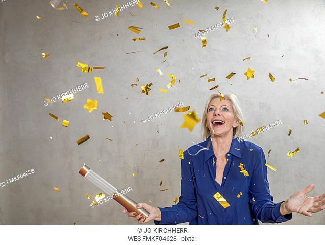 Portrait of amazed senior woman watching golden confetti