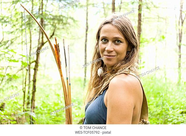 Portrait of smiling archeress in a forest