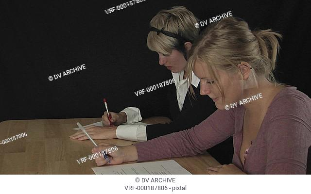 women sit at a table and fill out paperwork