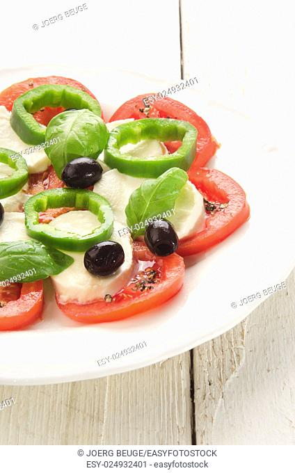 summer salad make from tomato, mozzarella, black olive, green chili and basil on a white plate