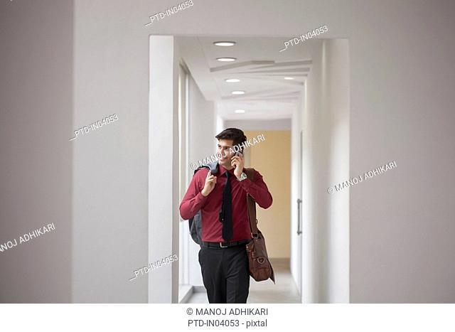 India, Man walking down corridor and talking on phone