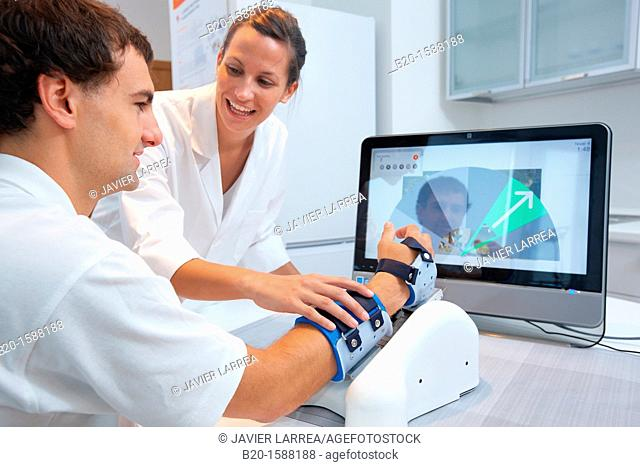 Investigator and patient with assistive robot for upper limb rehabilitation at home  This device is particularly suitable for patients who have suffered a...