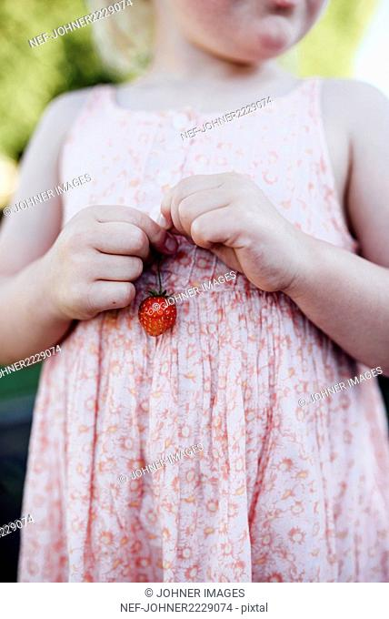 Girl holding strawberry