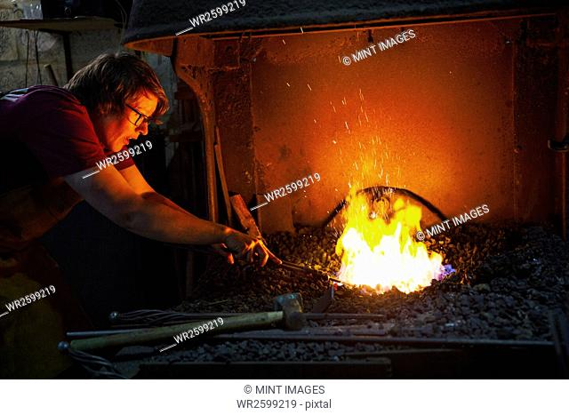 A blacksmith using tongs to heat something in a furnace