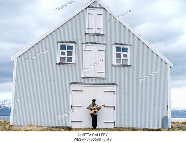 Iceland, young man playing guitar, wooden house