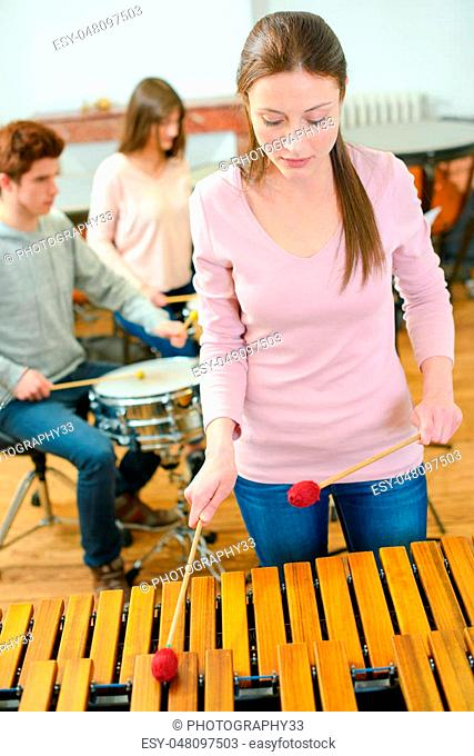 woman playing wooden xylophone
