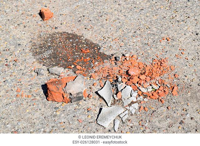 The broken bricks and pieces of slate on asphalt. Construction garbage