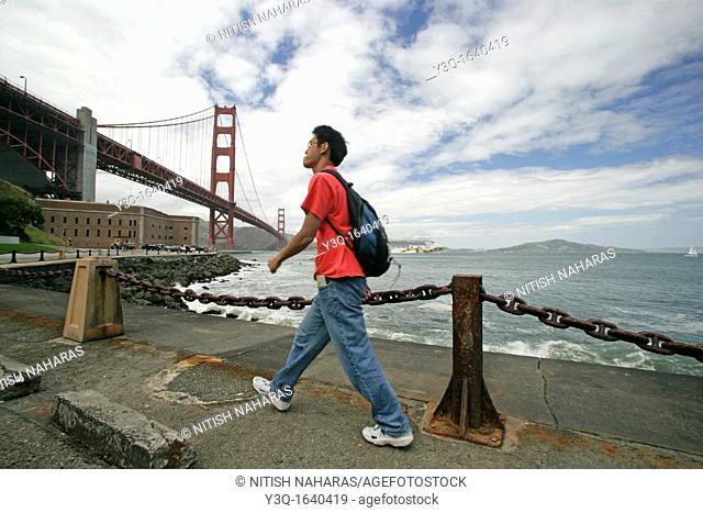A tourist walks to Fort point just under Golden Gate bridge in San Francisco, California  Slight motion blur