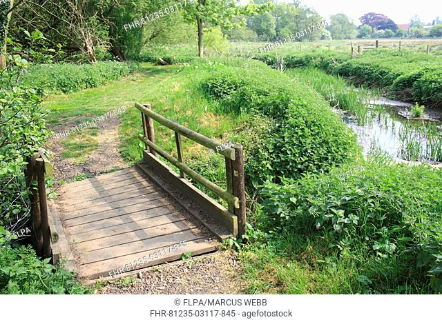 Wooden footbridge on footpath beside lowland river, River Rattlesden, Stowmarket, Suffolk, England, april