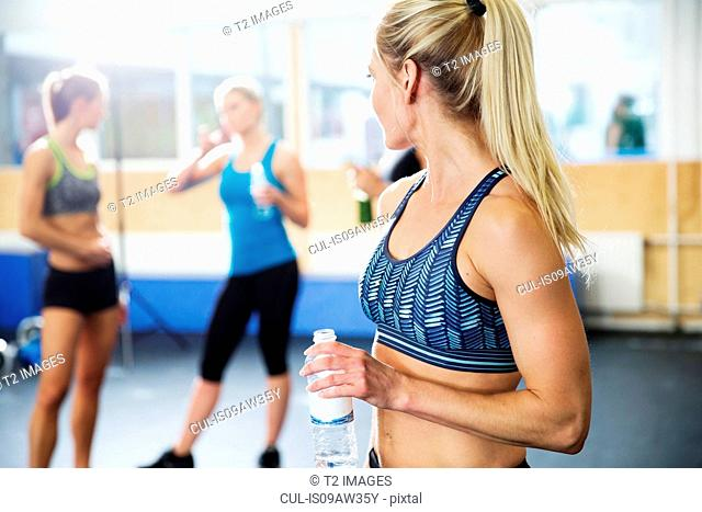 Woman drinking bottled water in gym