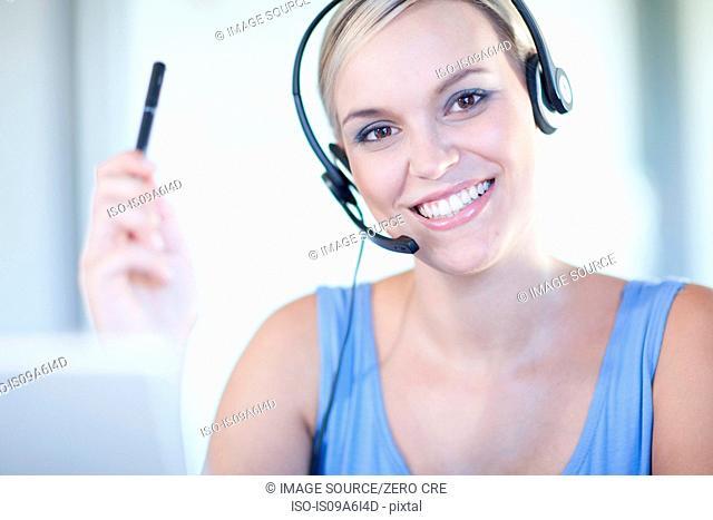 Businesswomen wearing headset at desk