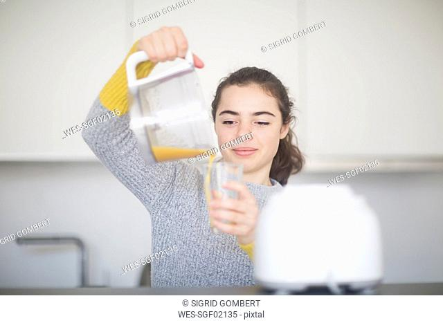 Portrait of smiling woman pouring freshly squeezed orange juice into a glass in the kitchen