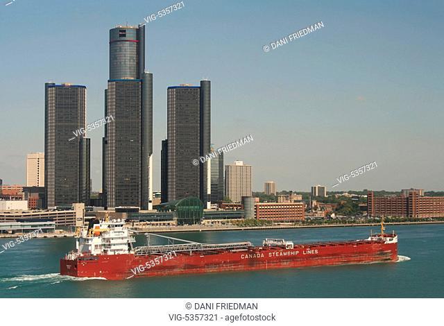 A large bulk carrier cargo ship travels along the Detroit River with the General Motors Building (Renaissance Center) in downtown Detroit, Michigan